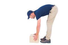 Side view of delivery man picking cardboard box Royalty Free Stock Image