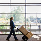 Side view of delivery woman pushing stack of boxes Stock Photography