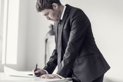 Side view of a designer or draftsman using ruler and pencil while working at the plan. Of a difficult project in the office, toned retro effect stock photos