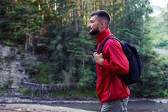 Determined bearded man hiking with backpack Stock Images