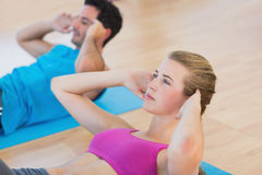 Side view of determined young couple doing sit ups. Side view of a determined young couple doing sit ups at a gym Royalty Free Stock Image