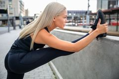Determined Young Woman Stretching Leg On Railing In City stock images