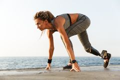 Side view of disabled athlete woman with prosthetic leg. Starting to run outdoor at the beach royalty free stock image