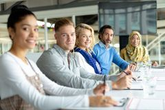 Business people looking at the camera during a business meeting in a modern office. Side view of diverse business people looking at the camera during a business royalty free stock photos