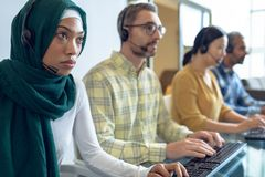 Customer service executives talking on headset at desk. Side view of diverse customer service executives talking on headset at desk in office stock image
