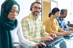 Customer service executives talking on headset at desk. Side view of diverse customer service executives talking on headset at desk in office stock photography