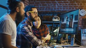 Men creating cartoon on computer. Side view of diverse group of people sitting at table with computer and coworking on creation of new cartoon stock video