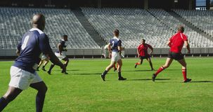 Rugby players playing rugby match in stadium 4k. Side view of diverse rugby players playing rugby match in stadium. They are passing ball to each other 4k stock video