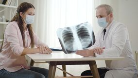 Side view of doctor in face mask explaining complications from Covid-19 viral disease on lungs x-ray to young Caucasian