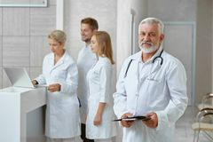Side view of doctor and his coleagues in clinic. Side view of four specialists in medical clinic. Man in white uniform with stethoscope holding documents royalty free stock photography