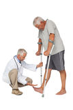 Side view of a doctor with senior man using walker Stock Photo
