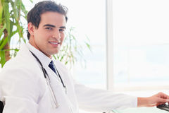 Side view of doctor sitting behind his desk Royalty Free Stock Photography