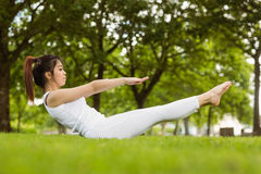 Side view of doing the boat pose in park Stock Photos