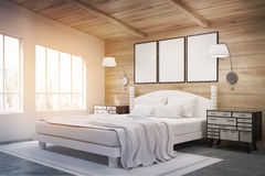 Side view of double bed with lamps, toned. Side view of a double bed in a room with wooden walls and ceiling. There are bedside tables and two large windows Stock Photo