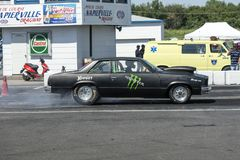 Drag car in action. Side view of drag car making a burnout at the starting line during the john scotti all out, august 20 2016 Stock Image
