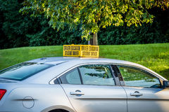 Side view of drivers ed car with yellow student driver sign on roof. Drivers ed car parked in high school parking lot royalty free stock image