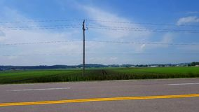 Side view driving by rural farmland in day. Driver point of view pov driving past countryside farm. Landscape stock video