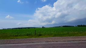 Side view driving by rural farmland in day. Driver point of view pov driving past countryside farm. Landscape stock video footage