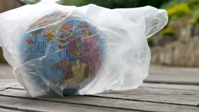 Side view of the Earth in polyethylene disposable package on wooden background. Concept of ecological problems. Stop. Garbage pollution, HD stock video