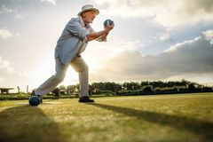 Side view of an elderly man playing boules royalty free stock images