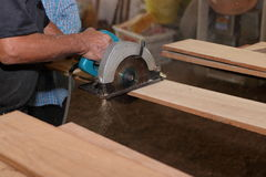 Side view of electric circular saw is being cut a piece of wood against hands of senior carpenter in carpentry workshop. Stock Image