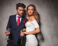 Side view of an elegant couple with champagne and glasses Royalty Free Stock Photo