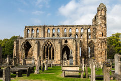 Side view of Elgin cathedral in northern Scotland. Elgin, Scotland - September 18, 2014: Landscaped side view of ruinous Elgin cathedral and cemetery on a sunny Royalty Free Stock Image