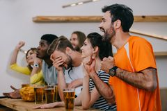 Side view of emotional multicultural friends gesturing by hands and watching football match at bar with beer glasses. And chips royalty free stock images