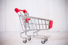 Side view of empty shopping cart. Empty shopping cart on white wooden background. Side view Royalty Free Stock Photography