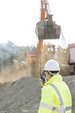 Side view of engineer using walkie-talkie at construction site Stock Images