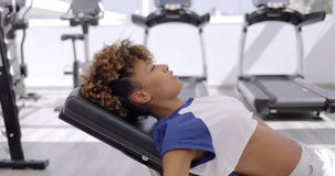 Concentrated sportswoman training with dumbbells. Side view of ethnic model in light clothing training chest muscles while training with dumbbells on bench in stock footage