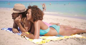Couple enjoying the music on beach. Side view of ethnic young happy man and woman lying on sandy beach and listening to music at seaside in sunny day stock video footage