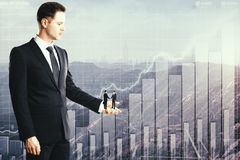 Partnership and economy concept. Side view of european businessman holding two tiny subordinated shaking hands on abstract city with business chart background Royalty Free Stock Image