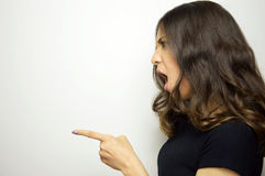 Side view of a excited surprised casual female pointing copyspace, over white background Stock Photo