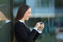 Profile of an executive using a phone on the street Royalty Free Stock Photos