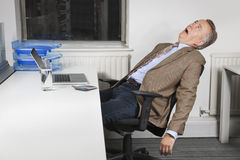Side view of exhausted middle-aged businessman in front of laptop in office Stock Image