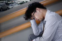 Side view of exhausted stressed young Asian business man feeling tired or disappointed with job. Royalty Free Stock Photos