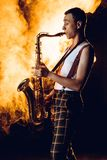 Side view of expressive professional saxophonist playing sax. In smoke royalty free stock images