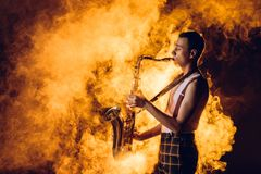 Side view of expressive stylish young jazzman. Playing saxophone in smoke royalty free stock image