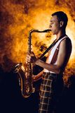 Side view of expressive stylish young musician playing saxophone. In smoke royalty free stock photo