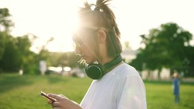 Side view of a fancy young girl in white T shirt typing on her mobile phone. Black headphones on her neck. Spending time. In the green park. Sun shines on the stock video footage