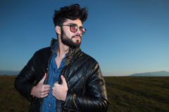 Side view of a fashion man holding his leather jacket Royalty Free Stock Image