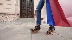 Side view of a fashion shopper woman legs walking with colorful shopping bags in the street. slow motion.  stock footage