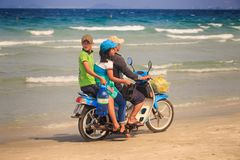 Side View Father Children Ride Old Motorbike on Beach. NHA TRANG/VIETNAM - APRIL 16 2017: Side view Vietnamese family father girl and boy ride old motorbike on Stock Photo