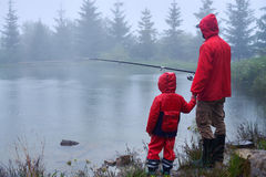Father and son fishing on the lake. Side view of father and son fishing on the lake together Royalty Free Stock Image