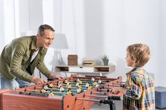 Side view of father and son playing table football together. At home stock image