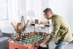 Side view of father and son playing table football together. At home Royalty Free Stock Photos