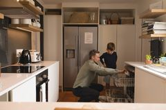 Father and son arranging utensils in dishwasher stock photos