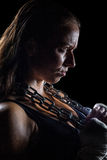 Side view of female angry athlete holding chain. Against black background Stock Image