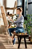 side view of female artist sitting on bench with paints and drawing picture royalty free stock images